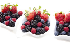 Fresh berries in bowls. Fresh berries in three ornate white bowls Stock Images