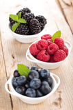 Fresh berries in bowls. Blueberries, blackberries and raspberries in small white bowls. With mint leaves. On wooden table Stock Photo