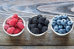 Fresh berries in bowls on a rustic wooden table Stock Photos