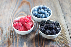 Fresh berries in bowls on a rustic wooden table Stock Photo