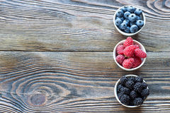 Fresh berries in bowls on a rustic wooden table Royalty Free Stock Photo