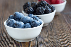 Fresh berries in bowls on a rustic wooden table Royalty Free Stock Photography