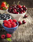 Fresh berries in bowls. Fresh berries in bowls on wooden background Stock Image