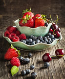 Fresh berries in bowls on wooden background. Royalty Free Stock Images