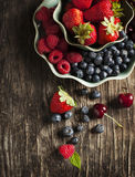 Fresh berries in bowls on wooden background. Fresh berries in bowls on dark wooden background Stock Photography