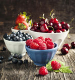 Fresh berries in bowls on wooden background. Royalty Free Stock Photo