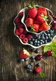 Fresh berries in bowls on wooden background. Royalty Free Stock Image