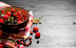 Fresh berries in a cup on the old fabric. Royalty Free Stock Images