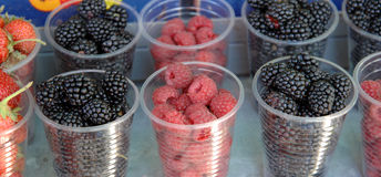 Fresh berries in a disposable plastic cup. Fro sale on a farmer market stock photos