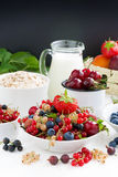 Fresh berries, fruit, cereal and milk. black background for text Stock Images