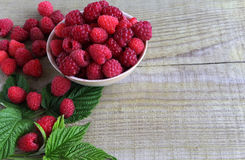 Fresh berries from the garden in a Cup on a wooden table. Raspberry With green leaves. Fresh and ripe berries of garden in a Cup on a wooden table. Raspberry Stock Photo