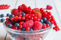 Fresh berries in a glass bowl. On wooden table Royalty Free Stock Photos