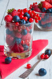 Fresh berries in a glass bowl. Fresh berries in a glass on wooden table Stock Image