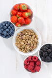 Fresh berries and granola on a white wooden background, vertical Royalty Free Stock Images