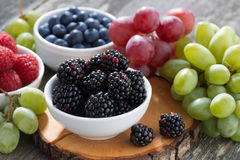 Fresh berries and grapes on a wooden table Royalty Free Stock Image