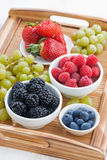 Fresh berries and green grapes on a wooden tray, top view Stock Image