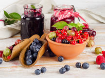 Fresh berries and jam. On a wooden table. Selective focus Stock Images