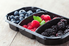 Fresh berries. Juicy fresh raspberries, blackberries and blueberries on old wooden background, selective focus Royalty Free Stock Photo