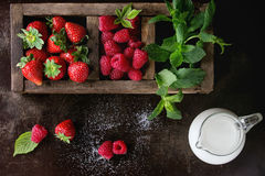 Fresh berries and mint. Fresh berries strawberry and raspberry with bunch of mint in old wooden sectioned box and jug of milk over dark textured background. Top Royalty Free Stock Photos