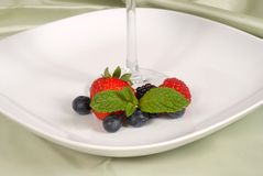 Fresh berries with mint surrounding the stem of a glass Royalty Free Stock Photography