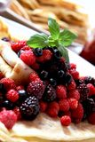 Fresh berries with pancakes. A plate of pancakes with fresh berries and a sprig of mint royalty free stock photography