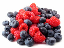Fresh berries in a pile. Fresh raspberries and blueberries mixed in a pile on white Stock Photos