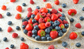 Fresh berries in a plate. On a brown background royalty free stock image