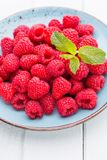 Fresh raspberries in a plate on a  vintage background. Fresh berries in a plate on a  wooden background. Flat lay, top view, copy space Royalty Free Stock Image