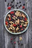 Fresh berries-raspberries,black raspberries, currants on a ceramic dish, rustic wooden dark background. Overhead, top view, flat l royalty free stock image