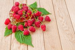 Fresh berries of raspberries on a plate on a wooden table.  Stock Photography