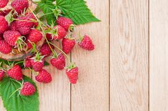 Fresh berries of raspberries on a plate on a wooden table.  Royalty Free Stock Photos
