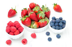 Fresh berries - strawberries, raspberries and blueberries. In a bowl on white background Royalty Free Stock Images