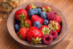Fresh berries , strawberries, raspberries, blueberries in a copper bowl. Standing on a wooden table Stock Images