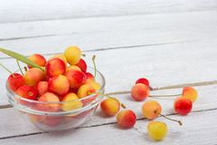 Cherry. Cherries in bowl. Fresh yellow cherry. Cherry on white wooden background. healthy food concept. Fresh berries. Sweet cherry background, on a rustic Stock Photography