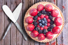 Fresh Berries Tart on Rustic Wooden Table with Serving Utensils Stock Images