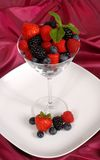Fresh berries topped with mint in and around a martini glass Royalty Free Stock Photography
