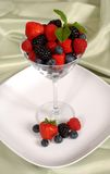 Fresh berries topped with mint in and around a martini glass res Royalty Free Stock Image