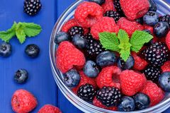 Fresh berries in a transparent bowl on table stock photo