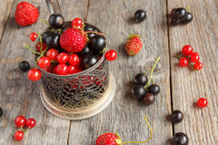 Fresh berries. Various summer berries in a bowl on rustic wooden table. Stock Photos