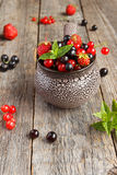 Fresh berries. Various summer berries in a bowl on rustic wooden table. Stock Photo