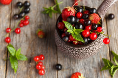 Fresh berries. Various summer berries in a bowl on rustic wooden table. Royalty Free Stock Image