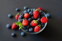 Fresh berries. Various summer berries in a bowl on rustic wooden table. Mixed berries in a bowl : strawberries, raspberries, blueberries and blackberries Royalty Free Stock Images