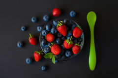 Fresh berries. Various summer berries in a bowl on rustic wooden table. Stock Images