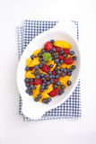 Fresh berries in a white plate. On a white background: raspberries, blueberries, peach Royalty Free Stock Photos