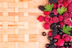 Fresh berries on a wicker backgound. Fresh raspberries, balckcurrents, mulberries on wicker backgound Royalty Free Stock Image