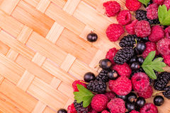 Fresh berries on a wicker backgound. Fresh raspberries, balckcurrents, mulberries on wicker backgound Stock Image