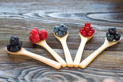 Fresh berries in wooden spoon on a rustic wooden table Stock Photo
