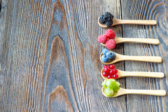 Fresh berries in wooden spoon on a rustic wooden table Stock Photos