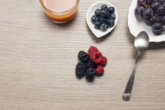 Fresh berries on a wooden table with a glass of juice. Antioxidants, detox diet, organic fruits Royalty Free Stock Images