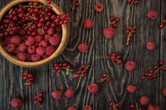 Fresh berries on wooden table. Fresh berries raspberry and red currant in bowl on wooden table Royalty Free Stock Photos